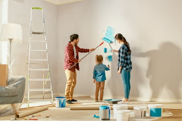 beautiful-young-family-are-showing-how-to-paint-walls
