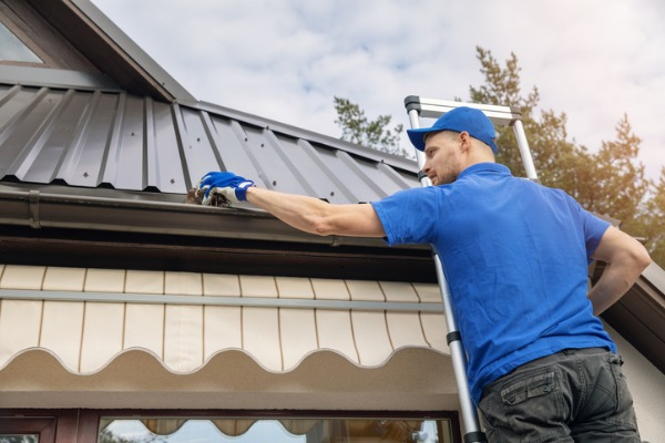 man standing and cleaning roof gutter