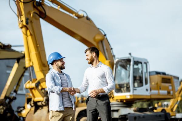 men handshake with heavy machinery background