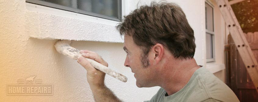 Man brushing paint on stucco wall