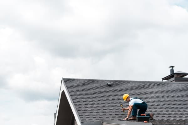 repairman-in-helmet-holding-hammer-while-repairing-roof