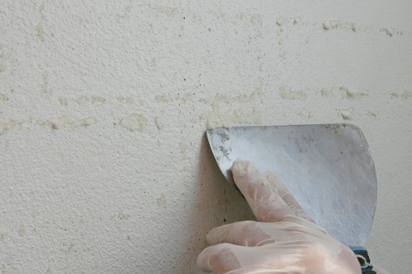 scraper in hands of a painter being used to remove sticky rough glue