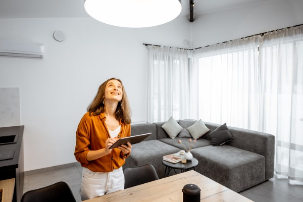woman controlling light with a tablet at home