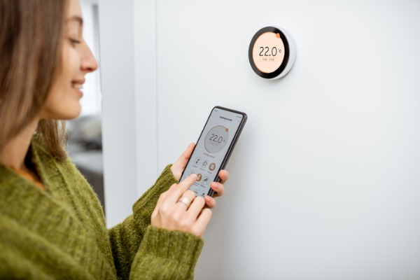 woman regulating heating temperature with phone and thermostat