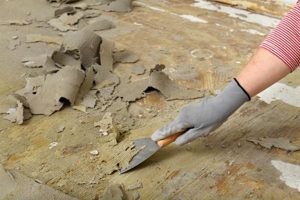 worker using scraper for cleaning floor