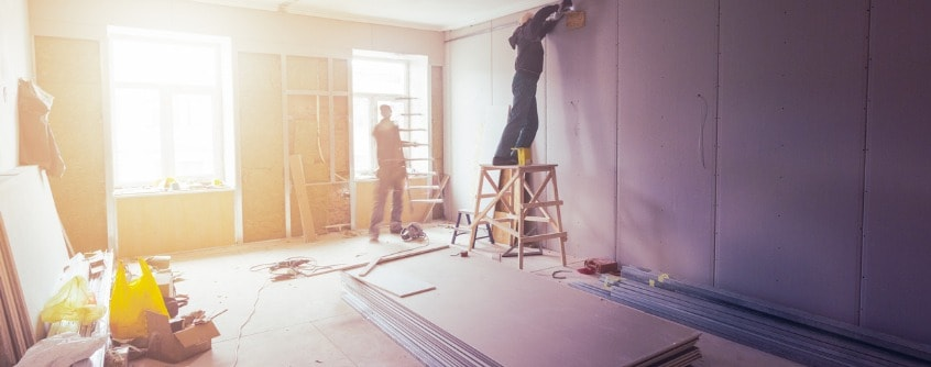 workers are installing plasterboard for gypsum walls in apartment